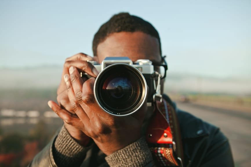 Portrait of an african american man in his 30's taking photos with a vintage camera with a bridge in the background