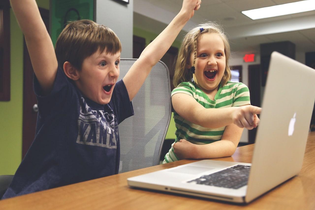 children celebrating at computer